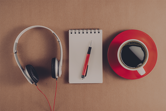 Photo of a pair of headphones on a desk with paper and pen, and a cup of coffee.