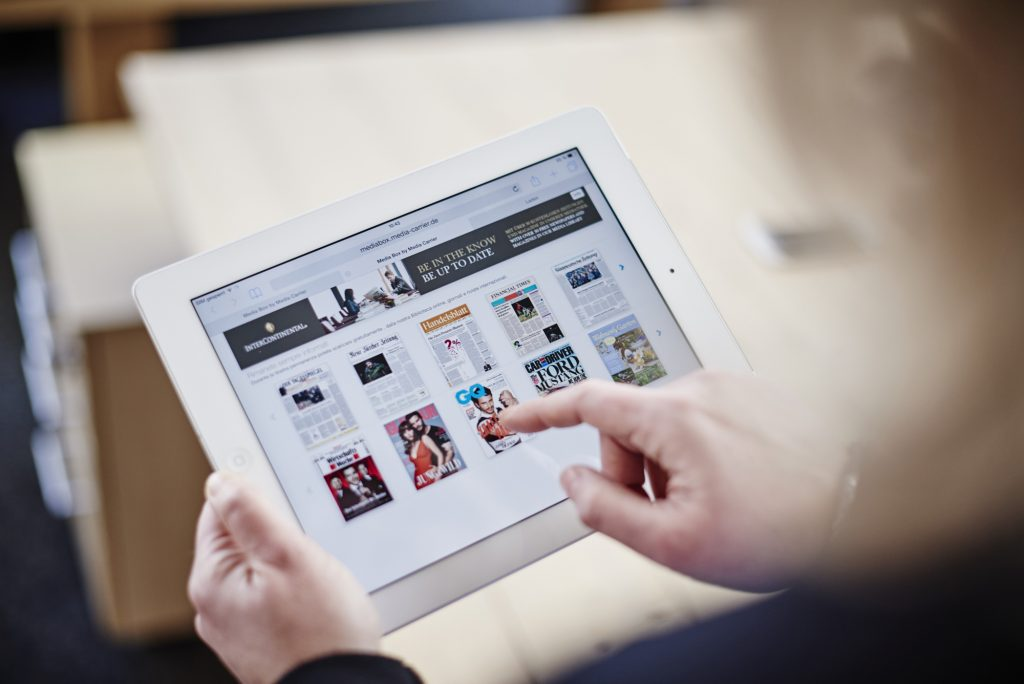 A person holds an iPad and is about to select a magazine from their reading list.