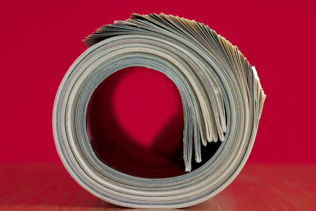 A rolled magazine forms a circle, set on a red background.
