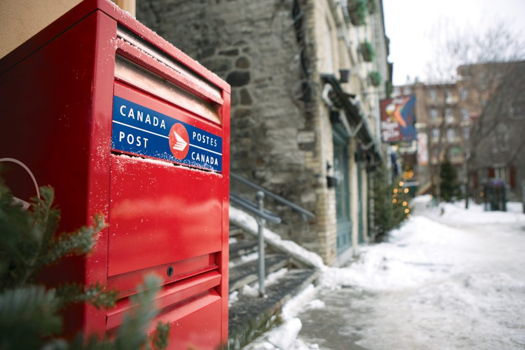 Photograph of a red Canada Post mailbox on a snowy street in Quebec City.