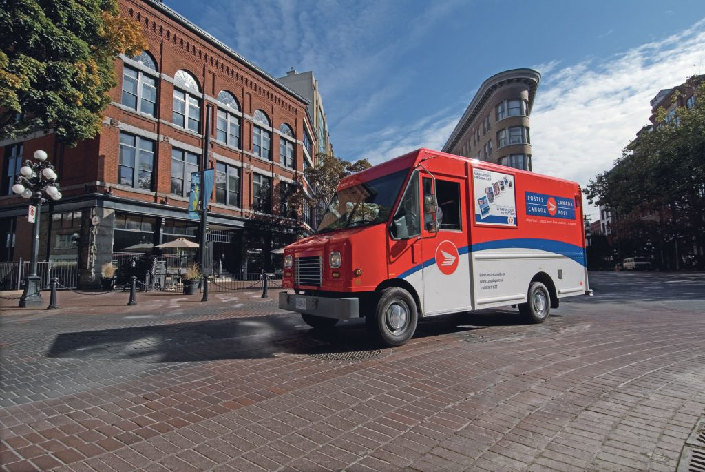 Photograph of a red Canada Post delivery truck on a sunny street in Gastown, Vancouver.