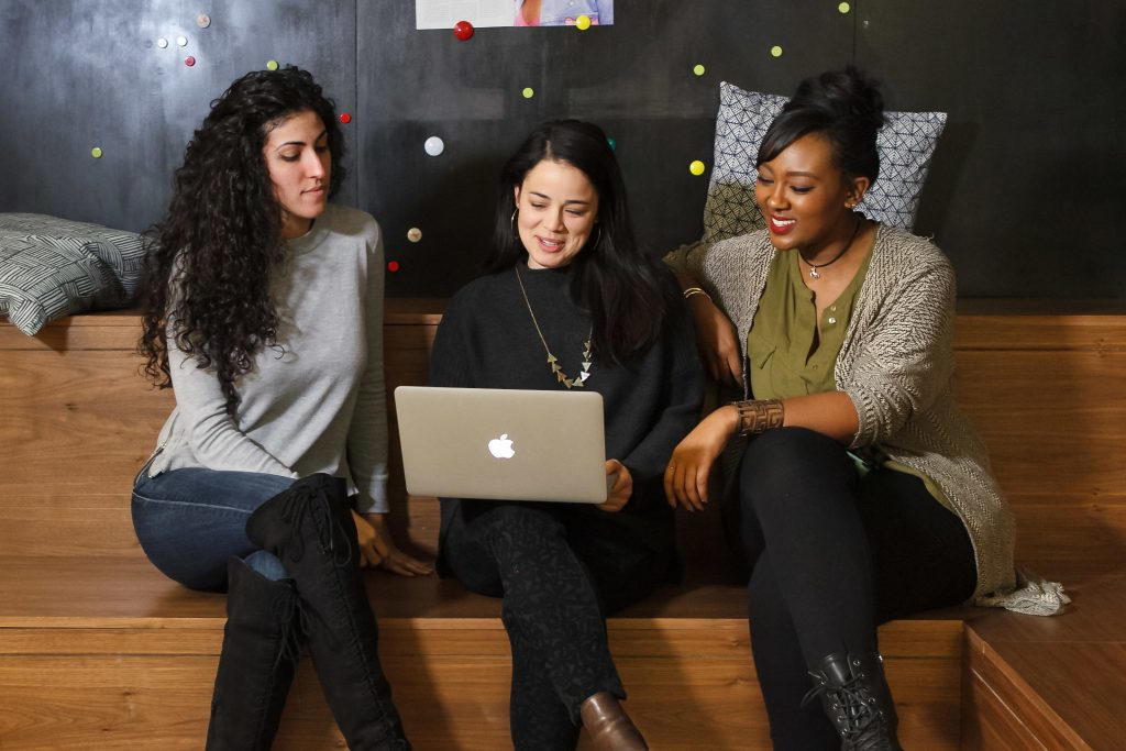 Three women sit around a laptop, smiling and talking with each other.