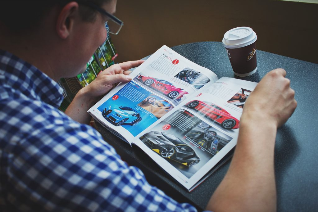 Man seated at a table reading a car magazine, with a coffee cup within easy reach.