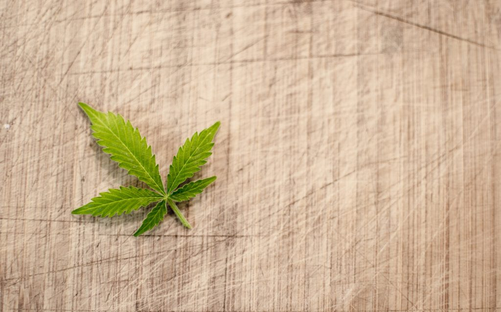 A single cannabis leaf sits on a wooden background.