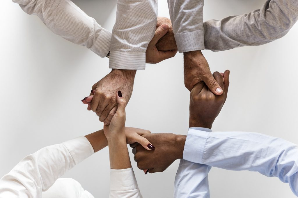 Interlocking hands show a close-working group of team members.
