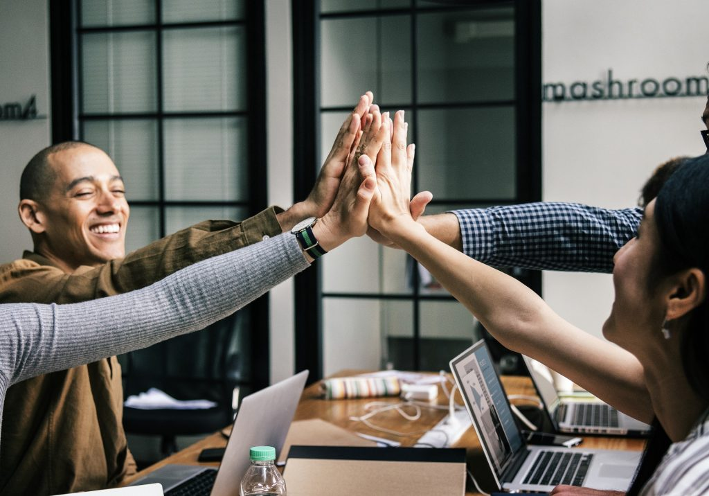 A group of team members high fives across a work desk.