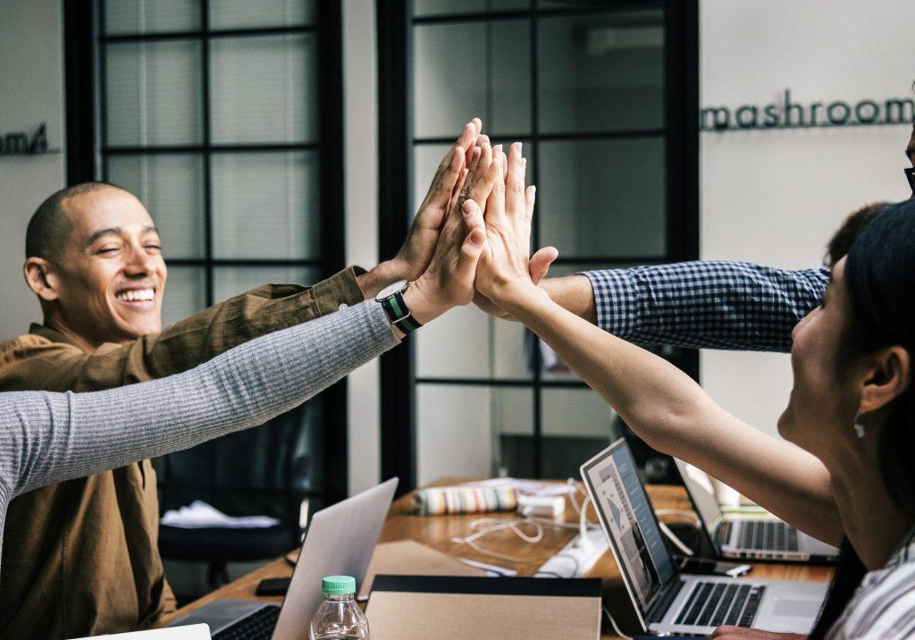 A group of team members high fives across a work desk.