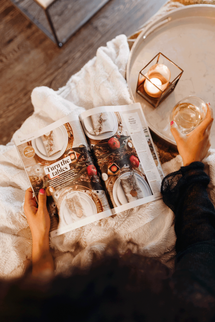 Woman relaxes with a candle and an open issue of a magazine.