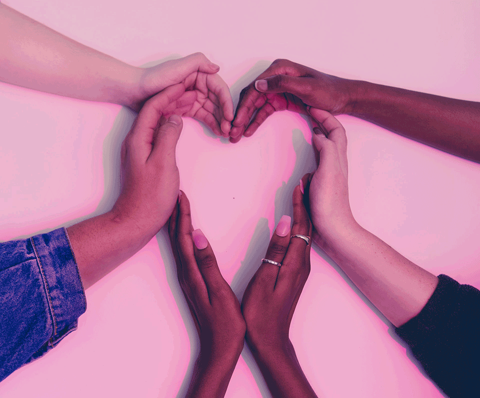 Six hands come together to form the shape of a heart.