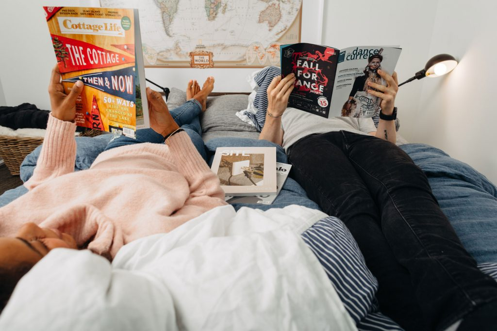 A couple lays on a bed together, each reading a favourite magazine.
